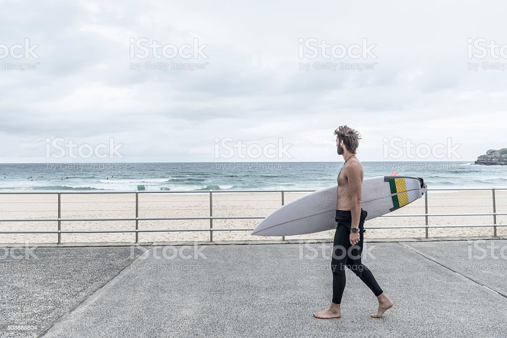 Man carrying surfboard along promenade, Bondi Beach stock photo