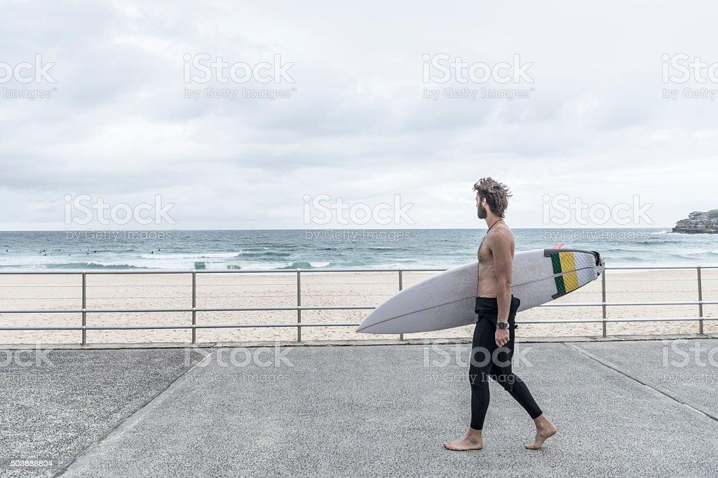 Homme transportant planche de surf sur la promenade, plage de Bondi - Photo