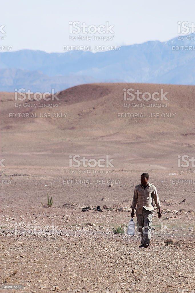 Man carrying water in desert stock photo