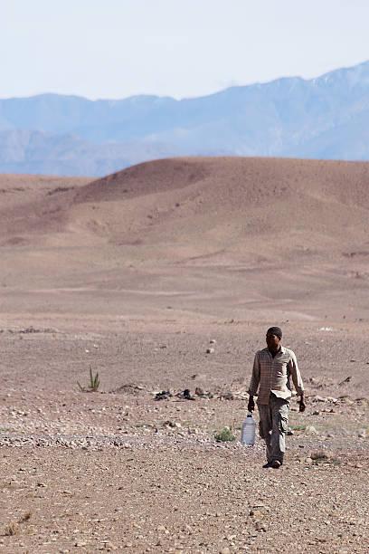 Man carrying water in desert foto