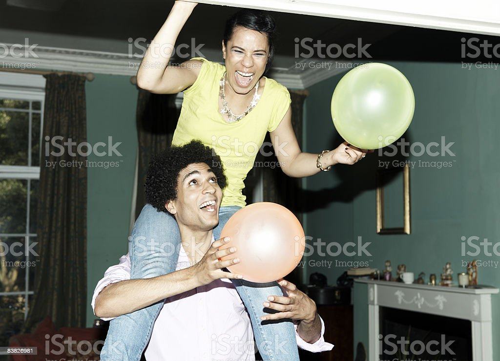 Man carrying woman on shoulders putting up balloon royalty-free stock photo
