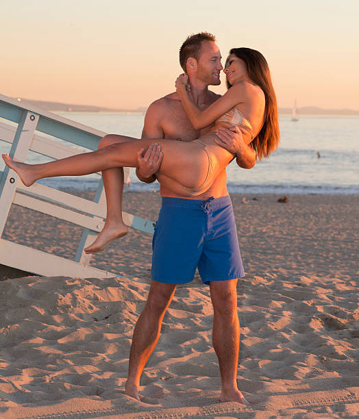 man carrying woman on the beach stock photo