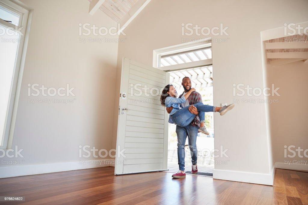 Mann trägt Frau über die Schwelle der Tür im neuen Zuhause – Foto