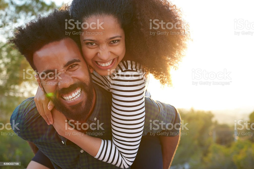 Man carrying young woman on his shoulders, looking to camera stock photo