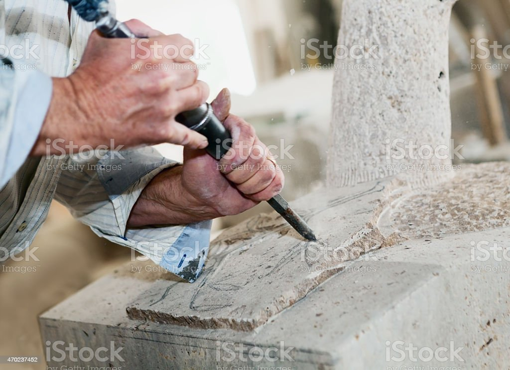man carves the marble with the chisel stock photo