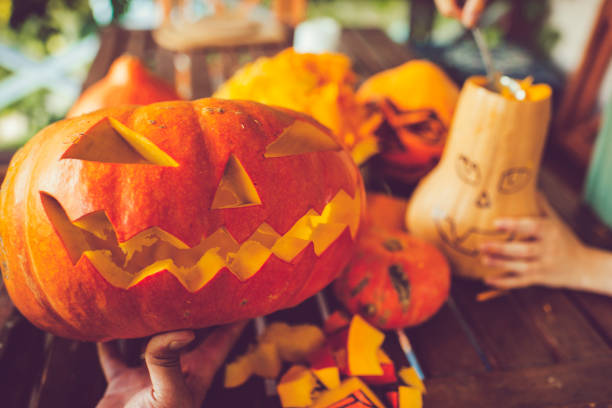 Man carving spooky face on a pumpkin in Halloween Man cutting spooky face on pumpkin in Halloween carving craft activity stock pictures, royalty-free photos & images