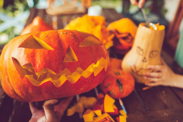 mann schnitzen gruselige gesicht auf einem kürbis in halloween - schnitzmesser stock-fotos und bilder