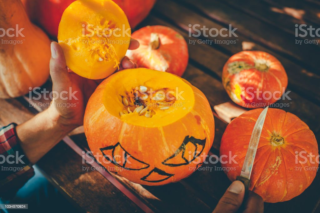 Man carving spooky face on a pumpkin in Halloween stock photo