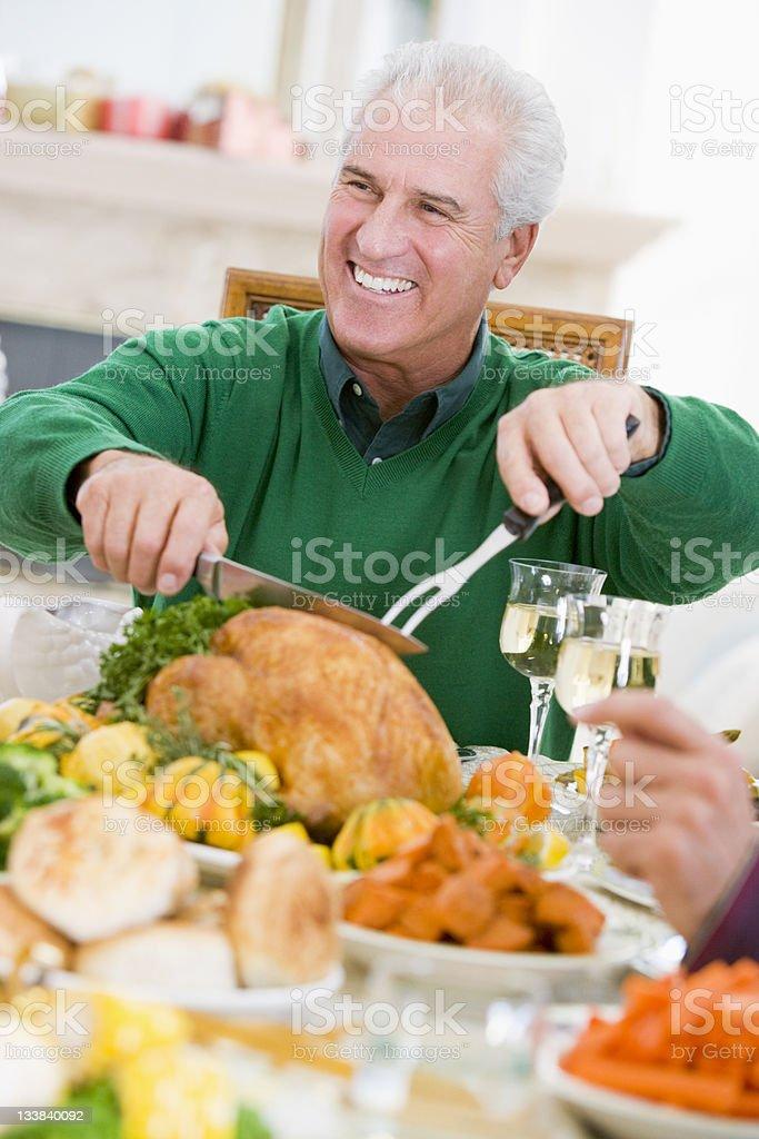 Man Carving Up Turkey Sitting At Dinner Table Having Christmas Dinner