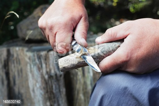 A man uses a bowie knife with a sharp blade to carve a wooden stick.