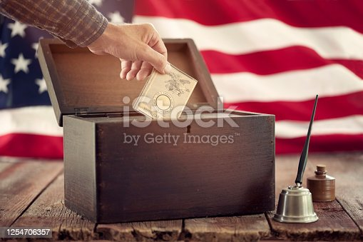 Man casting republican vote in a vintage ballot box against an American flag background