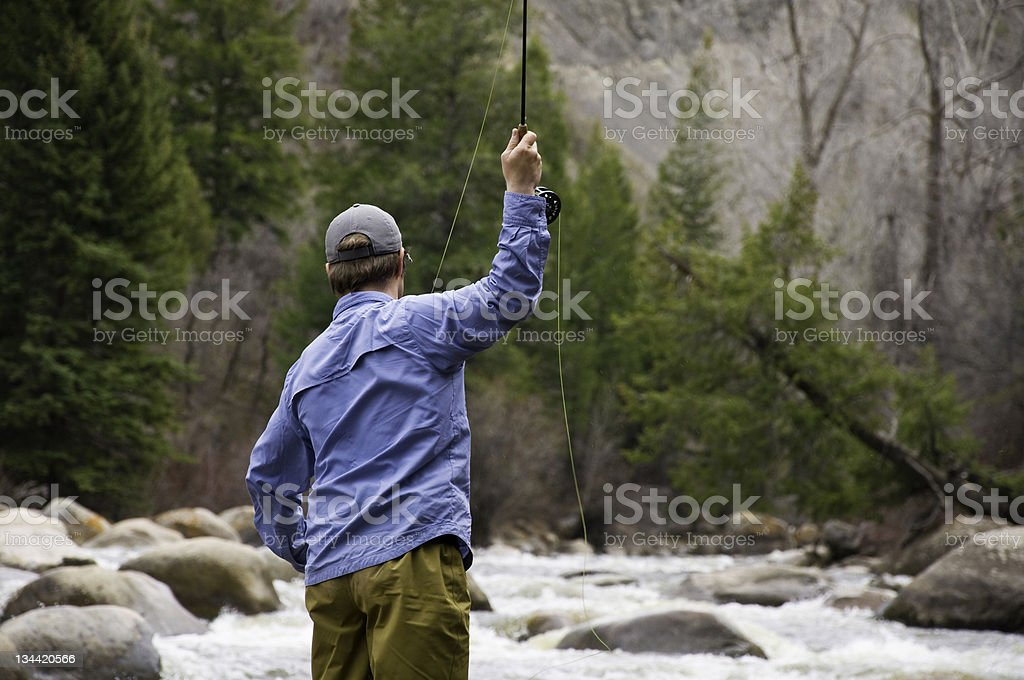 Man Casting While Fly Fishing stock photo