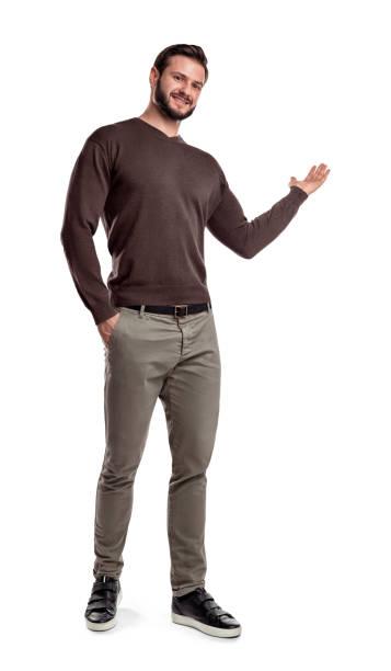 ein mann casual wear ist einen kleiner schritt, lächelt und zeigt etwas mit einen arm auf einem weißen hintergrund - russisch hallo stock-fotos und bilder