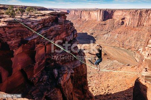 Slackliner is hanging on high-line between cliffs in Utah.
