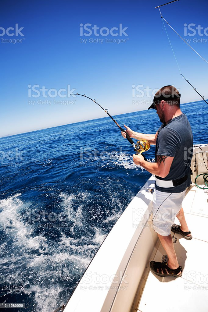 Man Catching Big Fish in Ocean stock photo