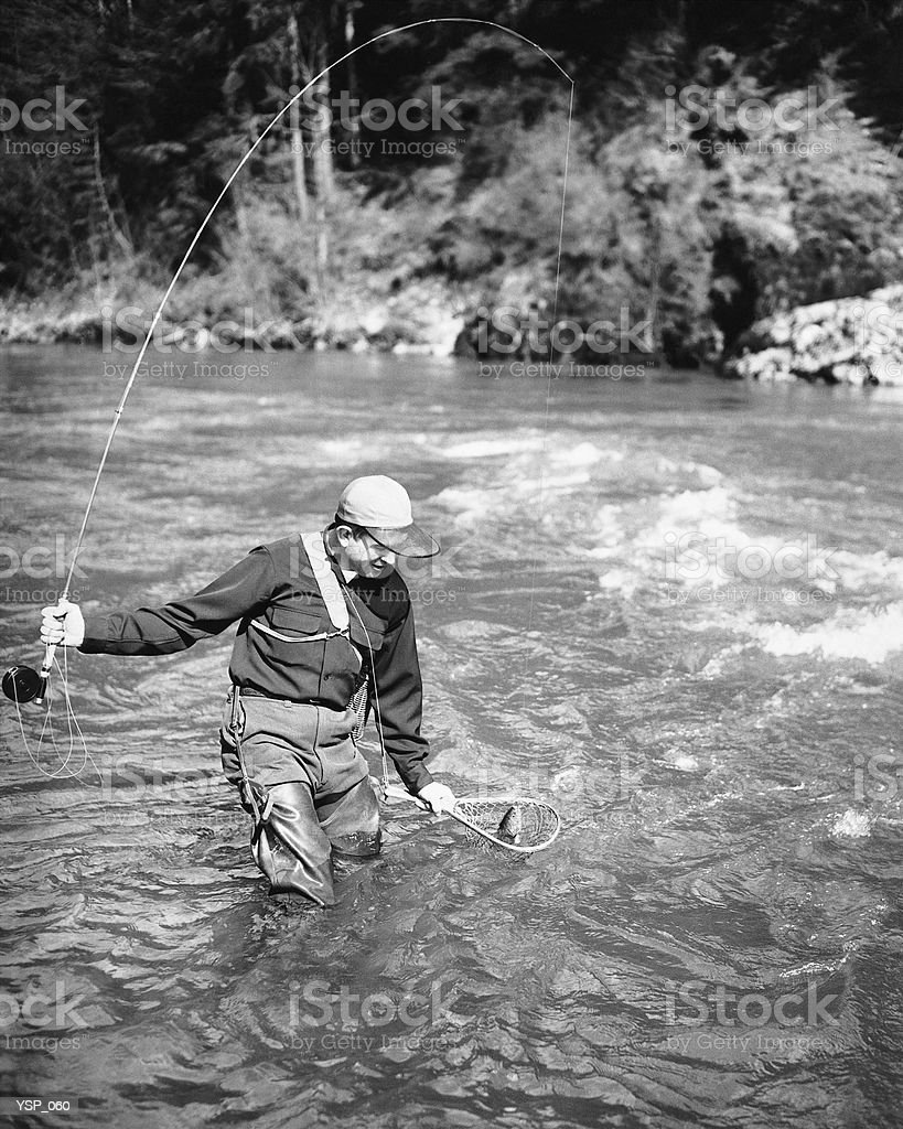 Man catching fish in river royalty-free stock photo