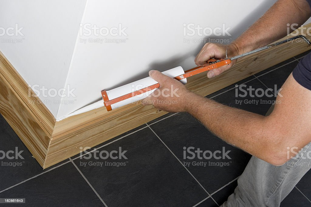 Man caulking wooden skirting in a new property stock photo