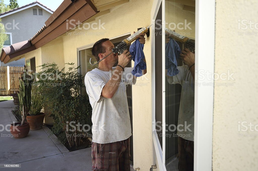 Man Caulks New Energy Efficient Windows stock photo