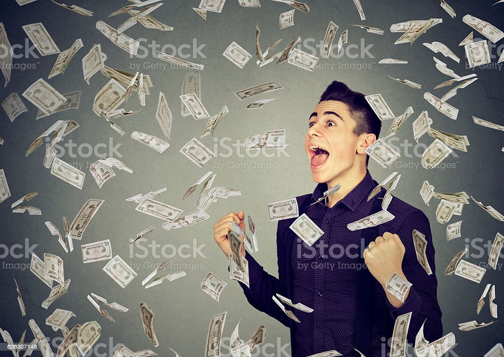 Man celebrates success under money rain falling down dollar banknotes stock photo