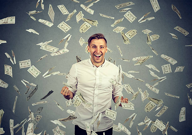 man celebrates success under money rain Portrait happy man exults pumping fists ecstatic celebrates success screaming under money rain falling down dollar bills banknotes isolated gray background with copy space. Financial freedom concept millionnaire stock pictures, royalty-free photos & images
