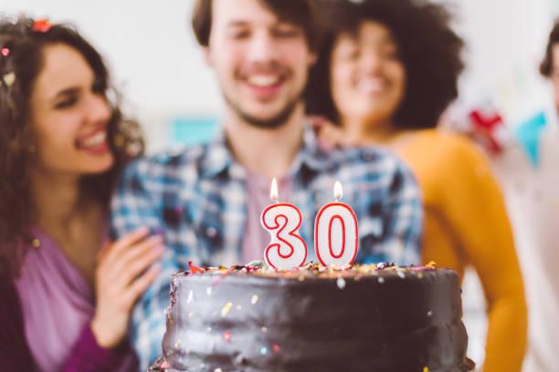 Man celebrating 30th birthday with friends stock photo