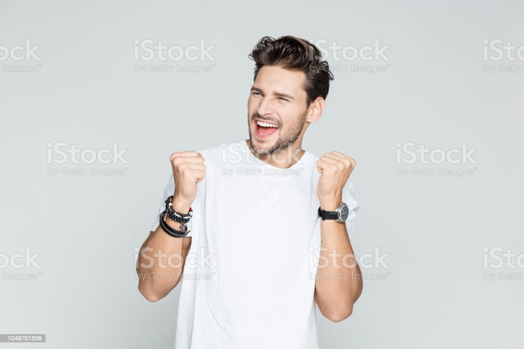 Man celebrating his success Portrait of young man with clenched fist and laughing on grey background 25-29 Years Stock Photo