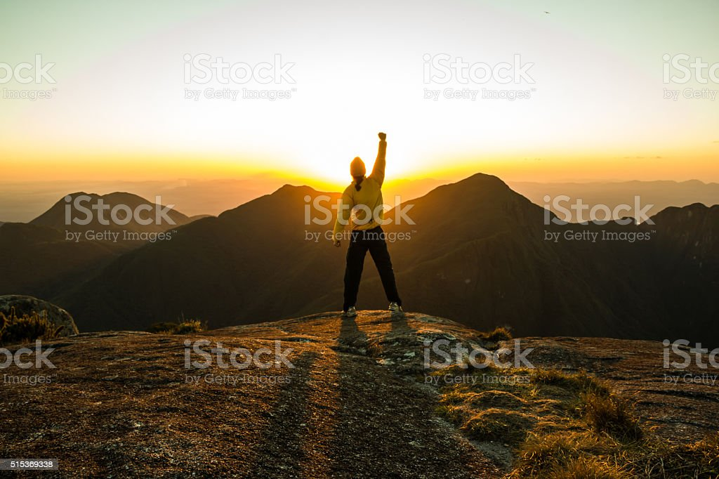 Man celebrating success on top of a mountain stock photo