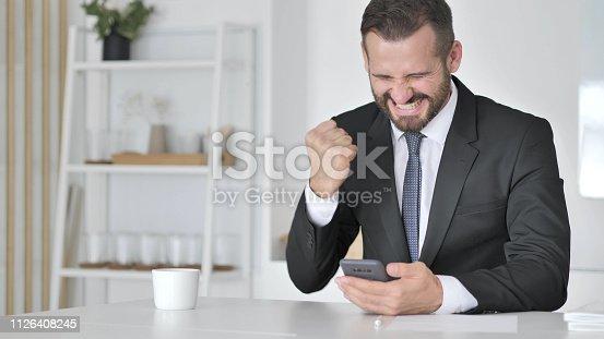 888751614 istock photo Man Celebrating Success while Using Smartphone 1126408245