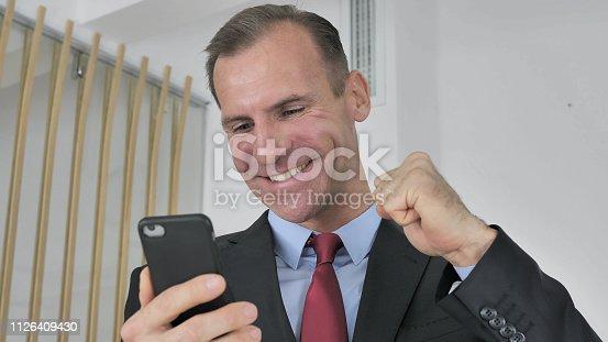 888751614 istock photo Man Celebrating Success while Using Smartphone 1126409430