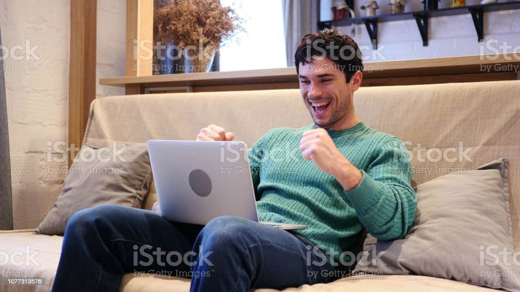 Man Celebrating Success while Working on Laptop, Sitting on Couch