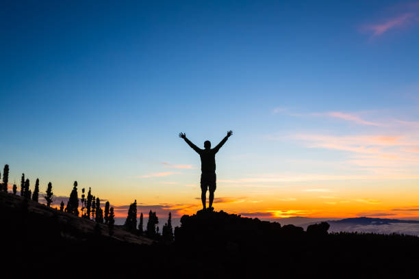 Man celebrating sunset with arms outstretched in mountains stock photo