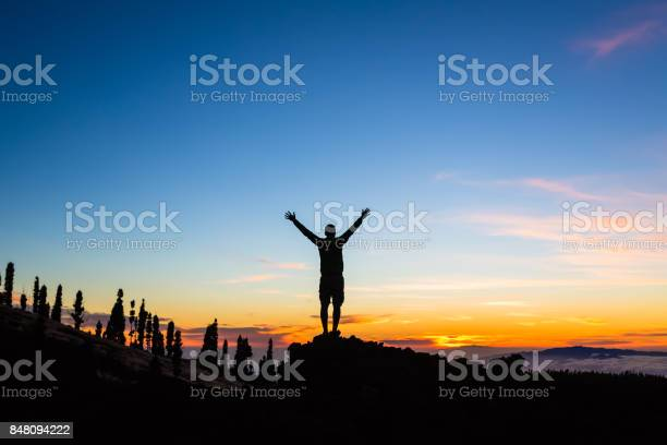 Photo of Man celebrating sunset with arms outstretched in mountains
