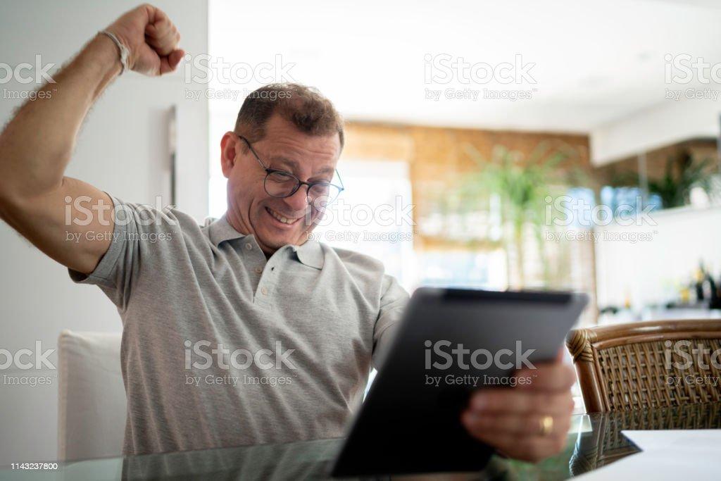 Man celebrating using digital tablet