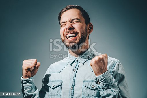 Half length portrait of casually dressed bearded business man holding fists up celebrating his success.