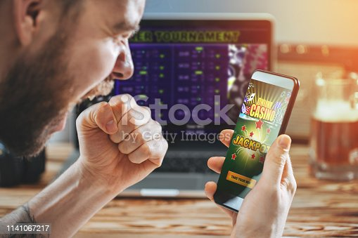 istock Man celebrating victory after making bets at bookmaker website 1141067217