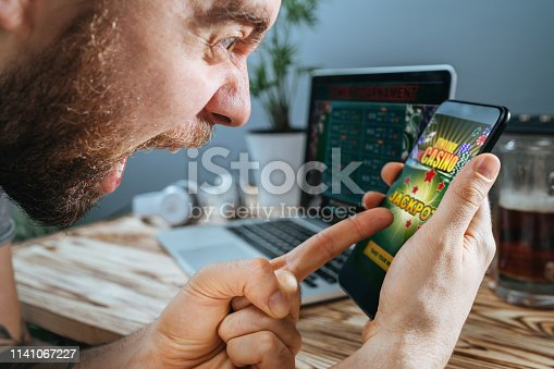 1032204252 istock photo Man celebrating victory after making bets at bookmaker website 1141067227