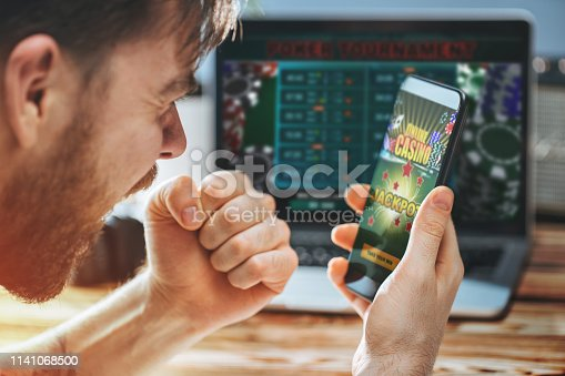 istock Man celebrating victory after making bets at bookmaker website 1141068500