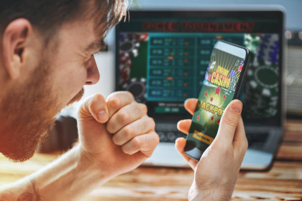 Man celebrating victory after making bets at bookmaker website Lucky man celebrating victory after getting jackpot in online casino. Poker tournament on the laptop screen on the background. game of chance stock pictures, royalty-free photos & images