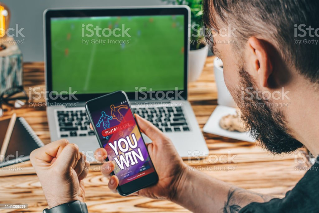 Lucky man celebrating victory after making bets using gambling mobile...