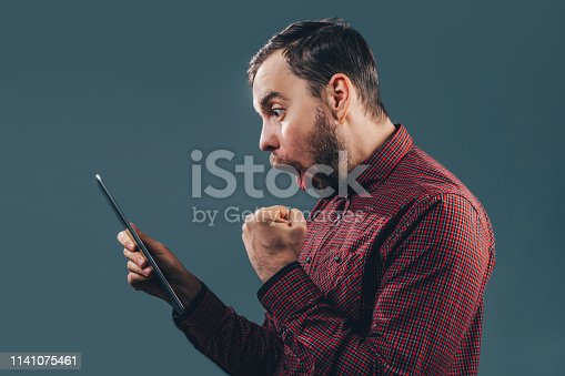 istock Man celebrating victory after making bets at bookmaker website 1141075461