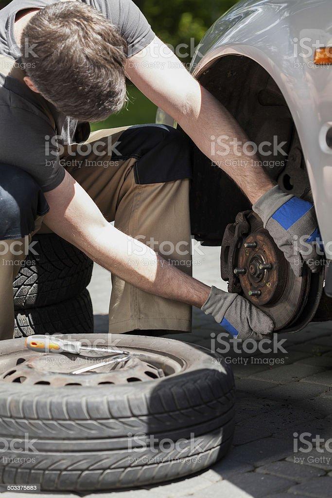 Man changing a car brakes stock photo