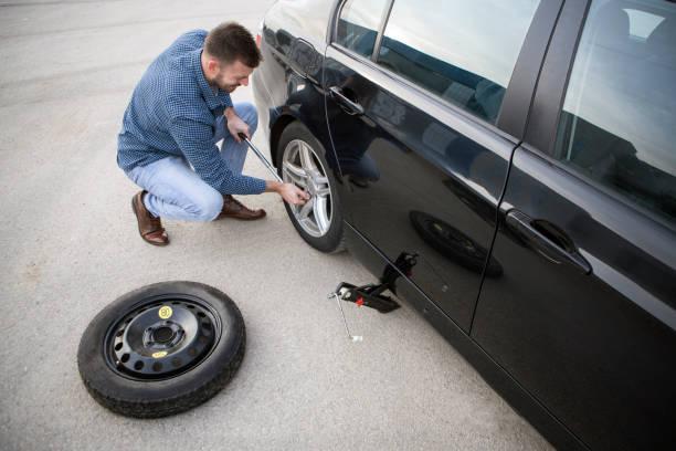Mann wechselt einen flachen Reifen – Foto
