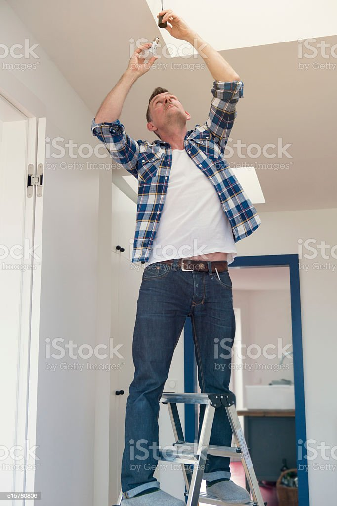man changing a lightbulb in living room stock photo