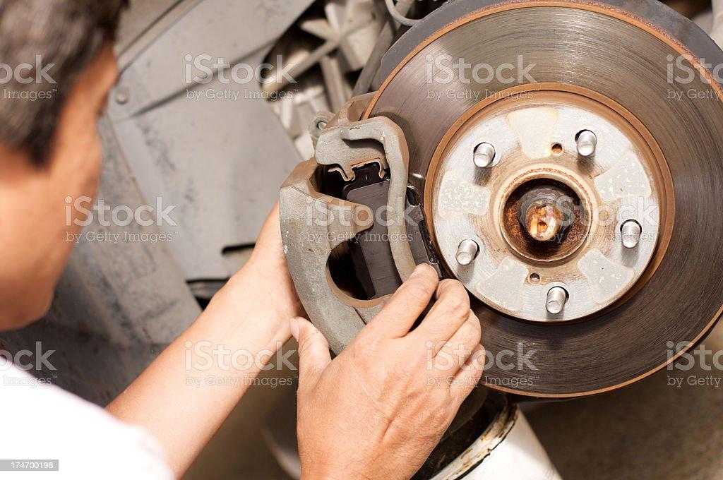 Man changing car brake pads on a car stock photo