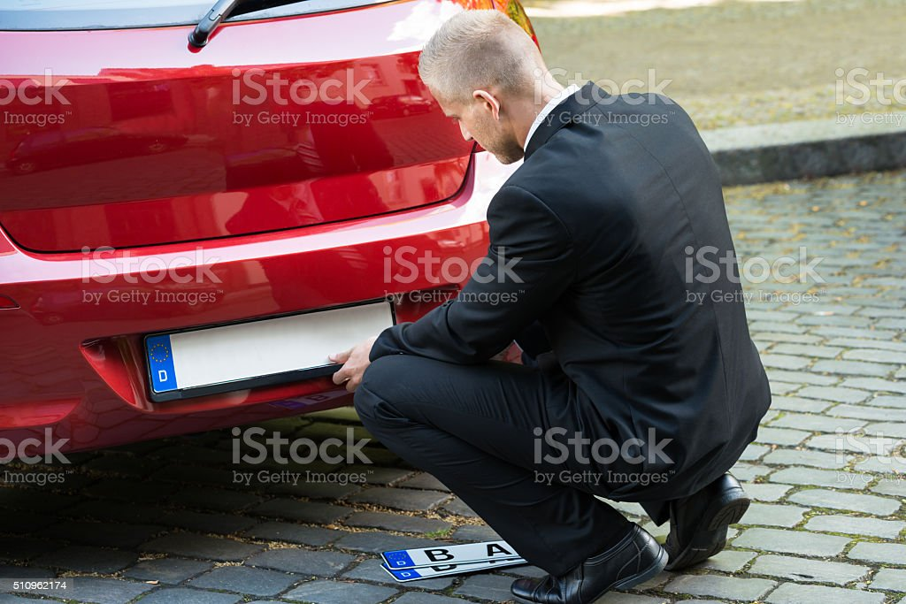 Man Changing Car's Number Plate stock photo