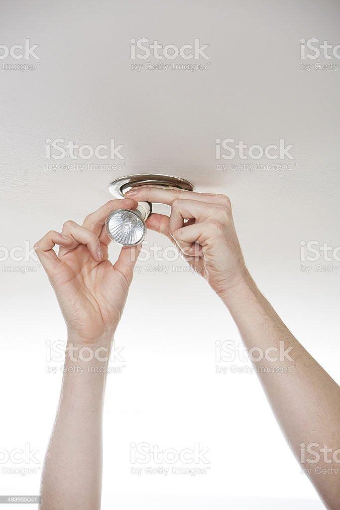 Man changing LED energy saving lightbulb stock photo