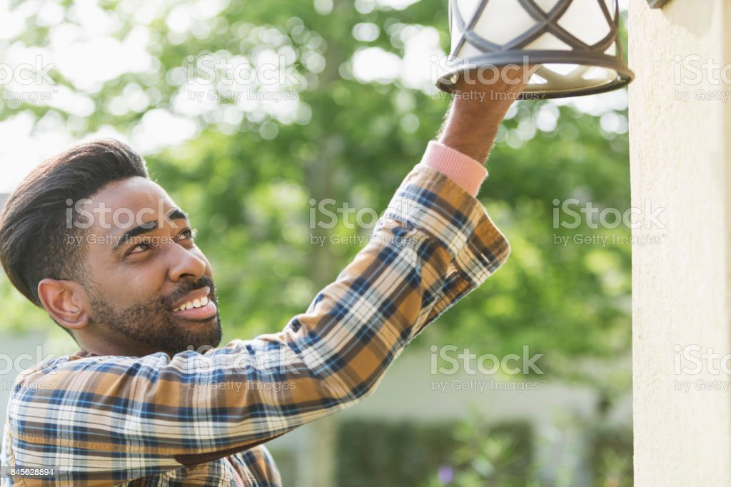 Man changing light bulb at house entryway stock photo