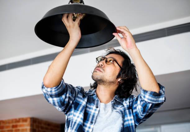 mann, die glühbirne zu hause ändern - japanische lampen stock-fotos und bilder