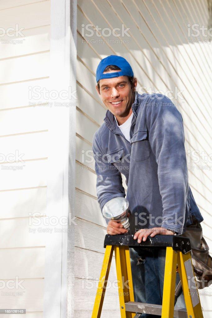 Man changing lightbulb on ladder stock photo