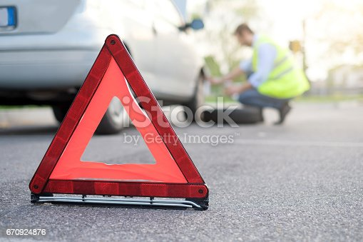 istock Man changing one flat tyre after vehicle breakdown 670924876